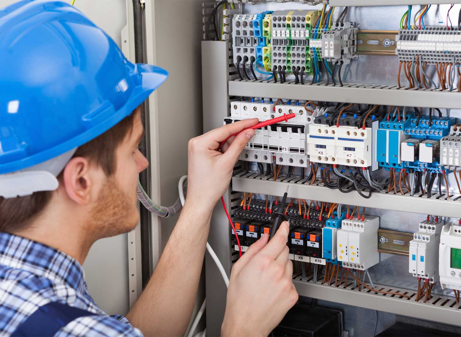 Industrial electrician testing control panel